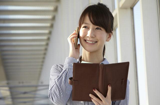 スケジュールを確認しながら電話をかける女性
