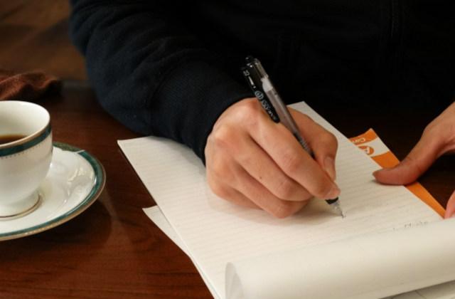 紙にメモをする人の手
