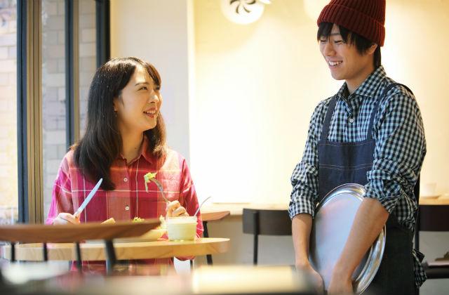カフェで会話をする店員と客