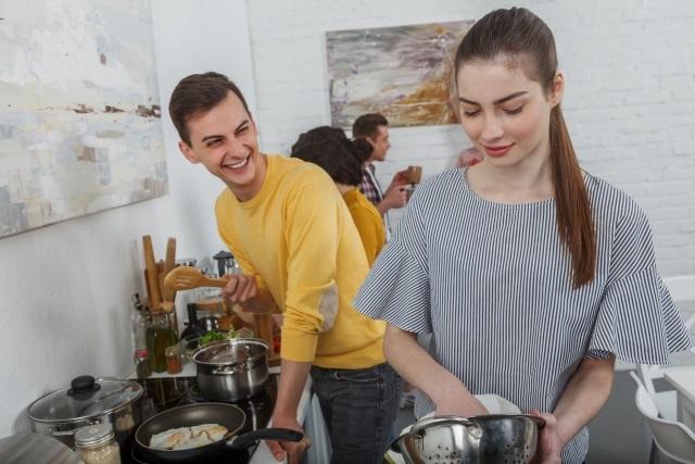 友達と一緒に料理をする男性